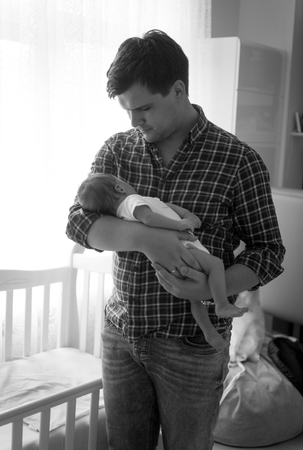 0 3 months: Black and white portrait of happy father holding little baby son