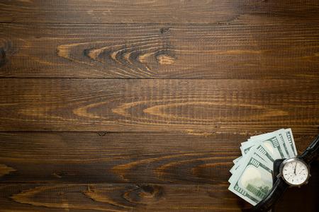 Background of money and watch lying on wooden desk.