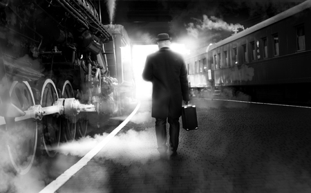 Black and white photo of man in vintage clothes walking on old railway station 스톡 콘텐츠