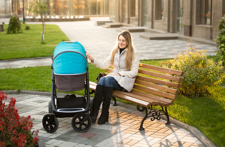 mother on bench: Beautiful mother sitting on bench at park and swaying baby stroller Stock Photo