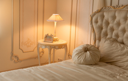 bedside lamp: Toned photo of luxurious bedroom with lamp on bedside table