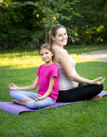Happy mother and smiling daughter practicing yoga and sitting back to back at park