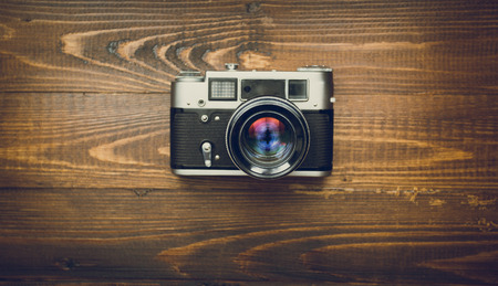 analog camera: Toned image of old analog camera with manual lens on wooden background