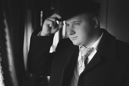 bowler hat: Closeup black and white portrait of man in bowler hat looking out train window Stock Photo