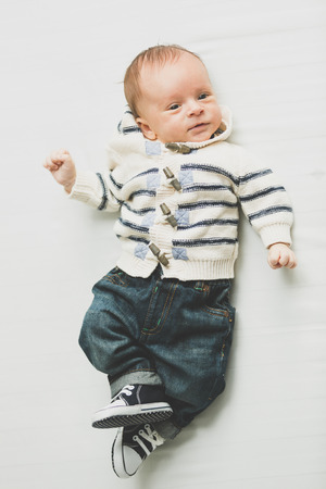 nappy new year: Toned photo of cute baby boy in jeans and sweater lying on bed