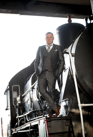 peron: Young man in gray suit posing on retro train