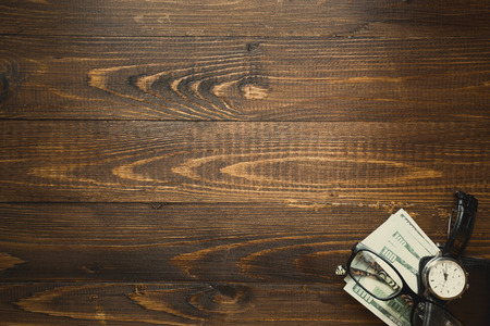 Stack of US dollars and hand watch over dark wooden background Stock Photo