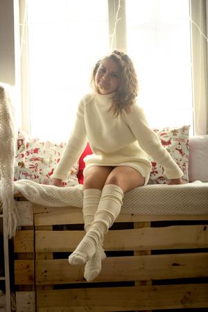 sueter: Foto en tonos de la mujer rizada linda en suéter y calcetines sentado en alféizar de la ventana