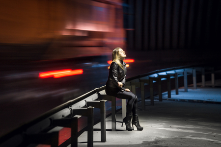 Lonely sad woman sitting at night at highway with cars rushing past her
