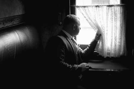 Monochrome portrait of elegant man sitting in train coupe and looking out of window
