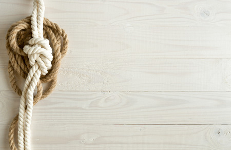tied knot: Toned image of ship ropes on white wooden background Stock Photo