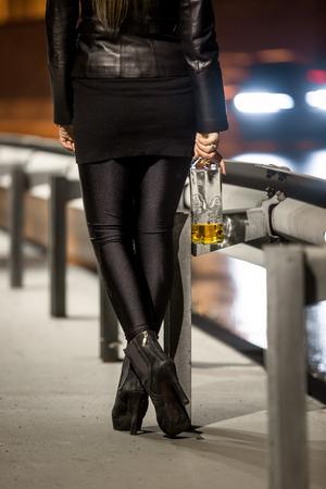 prostituta: Mujer con tacones altos celebración de la botella de whisky