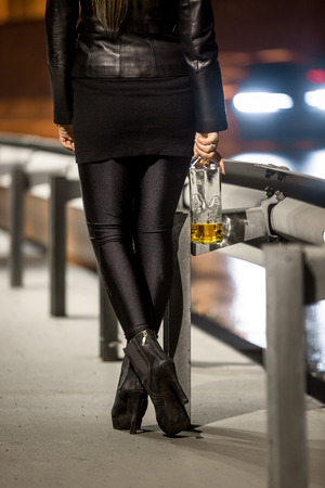 woman wearing high heels holding whiskey bottle