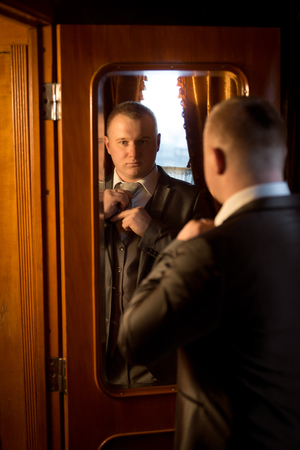 vistiendose: Retrato de tonos de caballero elegante mirando en el espejo y vestirse Foto de archivo