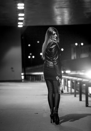 Schwarz-Weiß-Foto der schlanke Frau in der Nacht an der Straße aufwirft Standard-Bild