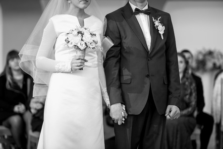desaturated: Closeup of bride and groom holding hands at wedding ceremony