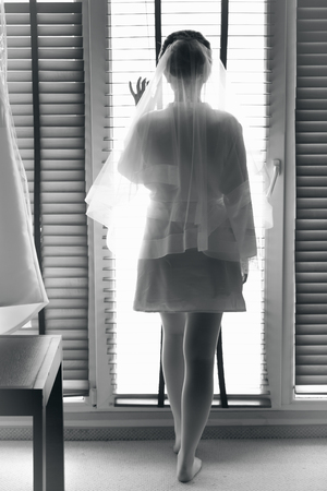 sexy bride: Black and white photo of sexy bride looking out of big window