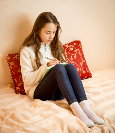 poems: Teenage girl sitting on bed and writing poems in notebook Stock Photo
