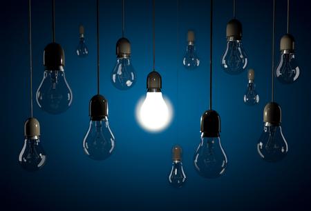 illuminating: One glowing bulb illuminating dark bulb hanging on wires on blue background