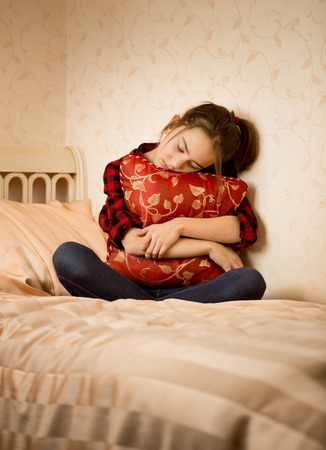 child sitting: Depressed teenage girl sitting on bed and embracing cushion Stock Photo