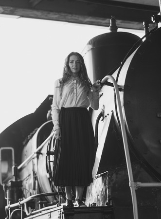 pipe dream: Black and white photo of elegant woman in dress posing on old steam locomotive
