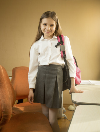 Beautiful girl in school uniform posing with bag at bedroom