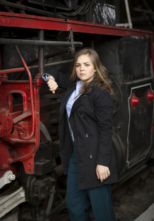 pipe dream: Portrait of beautiful young woman posing at big steam locomotive