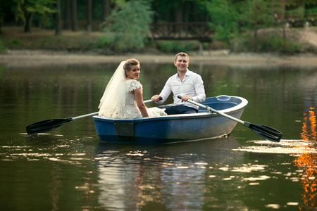 newly married couple: Newly married couple riding on old wooden boat on lake Stock Photo