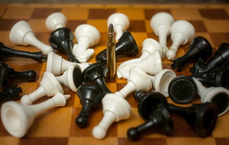 munition: One bullet among lying chess pieces Stock Photo