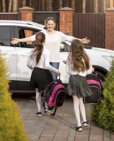 school girl uniform: Two cheerful schoolgirls running to mother meeting them after school Stock Photo
