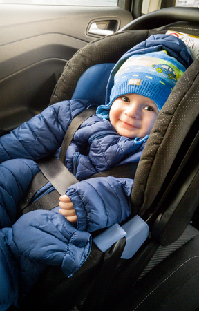 enfant banc: Portrait of cute smiling boy in hat sitting in car child seat
