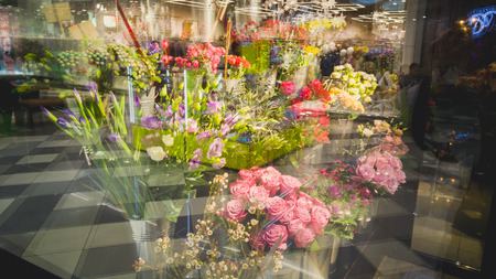 sidewalk sale: Toned photo of stands with flowers through store window