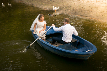 newly married couple: Happy newly married couple riding on rowing boat on lake