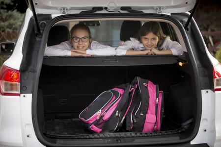 car trunk: Portrait of two smiling schoolgirls looking through open car trunk