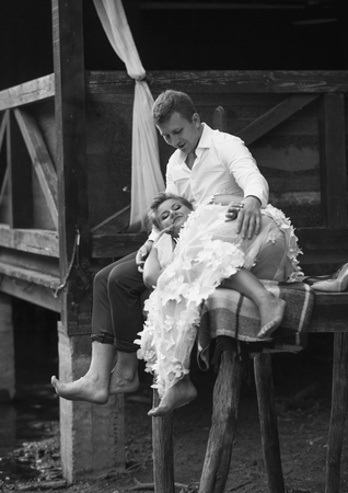 Black and white photo of bride and groom sitting on old wooden pier