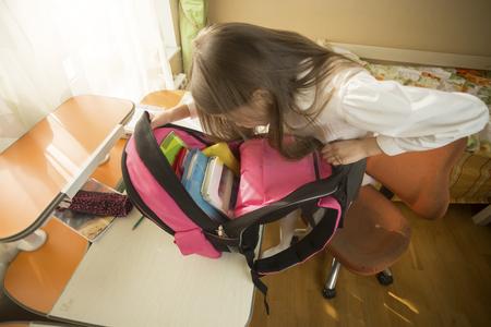 one room school house: Portrait of cute schoolgirl looking inside of her backpack