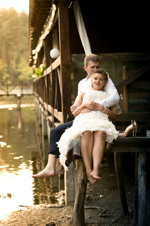 newly married couple: Happy newly married couple relaxing on old pier at forest Stock Photo