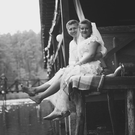Black and white photo of newlyweds sitting on pier and laughing
