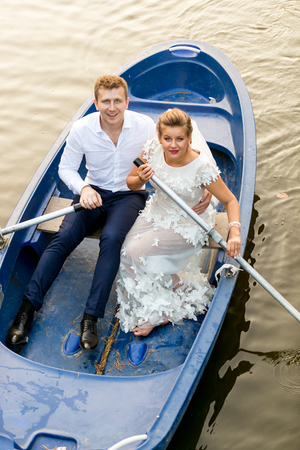 newly married: Happy newly married couple riding on rowing boat at evening