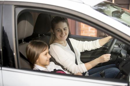 娘と一緒に学校に若い母親運転の車の肖像画 写真素材