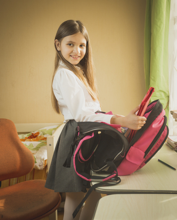 Portrait of cute smiling schoolgirl packing bag for school Stock fotó
