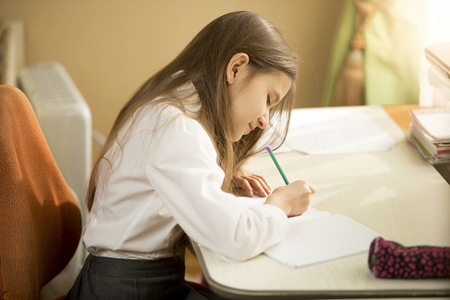 exercise book: Side view portrait of concentrated schoolgirl writing at exercise book