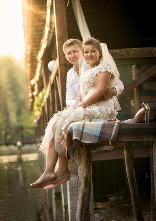 newly married couple: Happy newly married couple sitting on old wooden pier at sunny day
