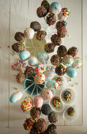 confectionary: View from top on beautiful colorful cake pops on wooden table at confectionary