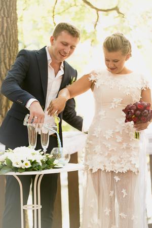 feier: Getönten Foto der schönen Braut und Bräutigam streuten Sand in den Gläsern bei Trauung Lizenzfreie Bilder
