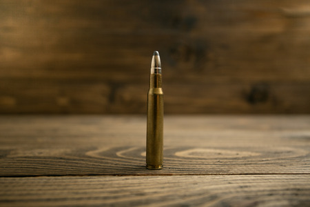 full jacket bullet: Closeup photo of riffle bullet on old wooden desk