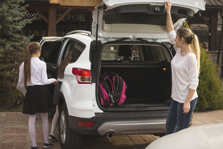 Young mother and two daughters getting in the car to go to school Standard-Bild
