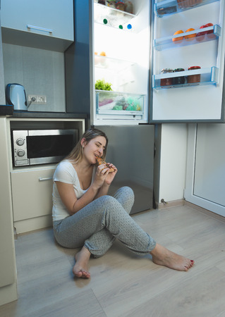 sleepless: Young sleepless woman sitting on kitchen floor next to open refrigerator and eating pizza