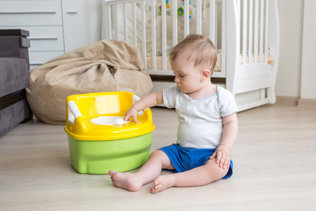 chamber pot: Cute 10 months old baby boy getting accustomed to using chamber pot