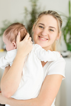 Portrait of beautiful smiling mother cuddling her 3 months old baby Stock Photo